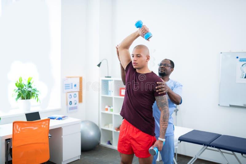 De mens met het aardige spieren doen oefent bezoekende sportentherapeut uit stock foto
