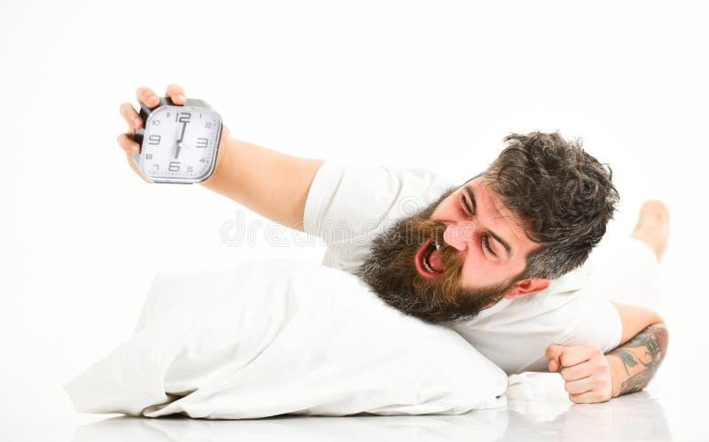 De mens met het schreeuwen gezicht ligt op hoofdkussen dichtbij wekker stock afbeelding