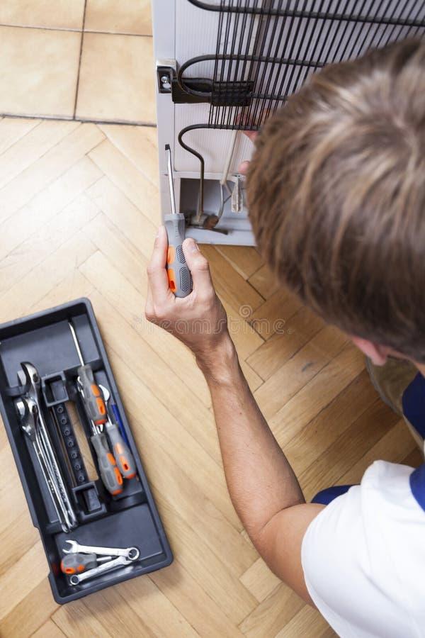 De mens met hulpmiddelen herstelt de koelkast stock foto's