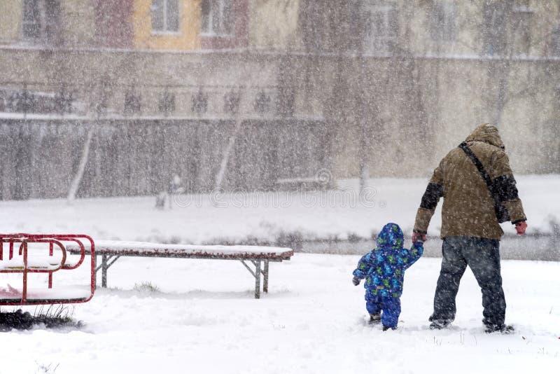De mens met kind maakt hun manier door de blizzard in de stad royalty-vrije stock foto