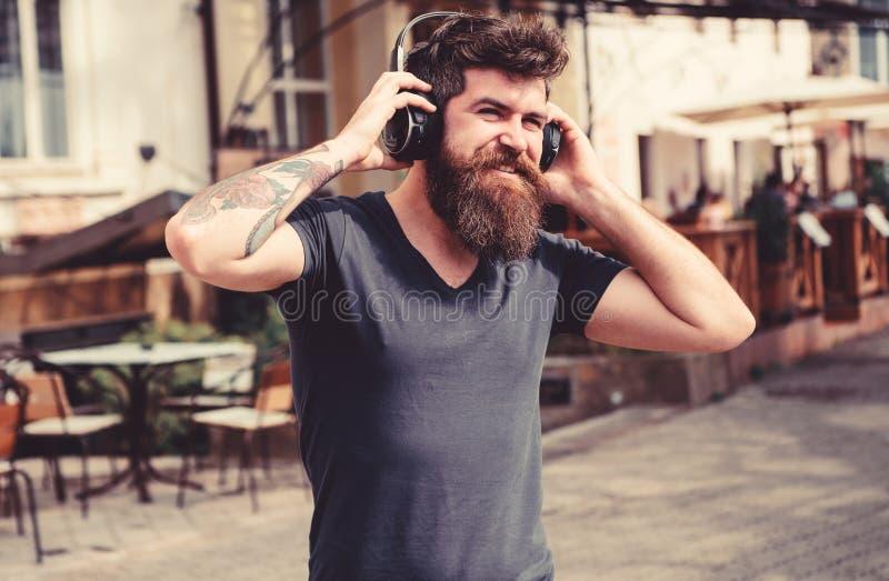 De mens met lange baard en de snor met draadloze hoofdtelefoons op hoofd, defocused stedelijke achtergrond Hipster met hoofdtelef stock fotografie