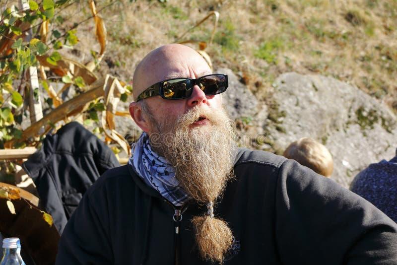 De mens met lange baard glimlacht, en geniet van de laatste stralen van zonneschijn in de herfst, oogstfestival royalty-vrije stock fotografie