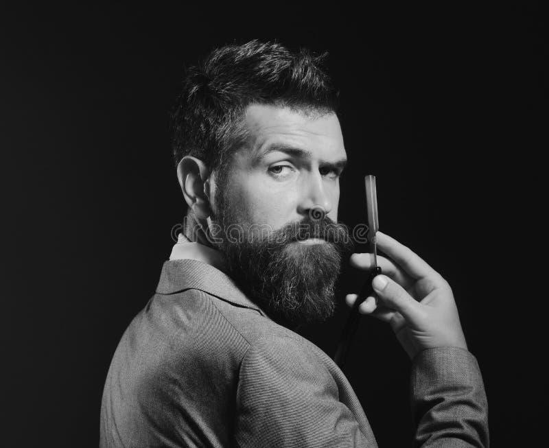 De mens met lange baard houdt blad voor scheermes Herenkapper reclame stock fotografie
