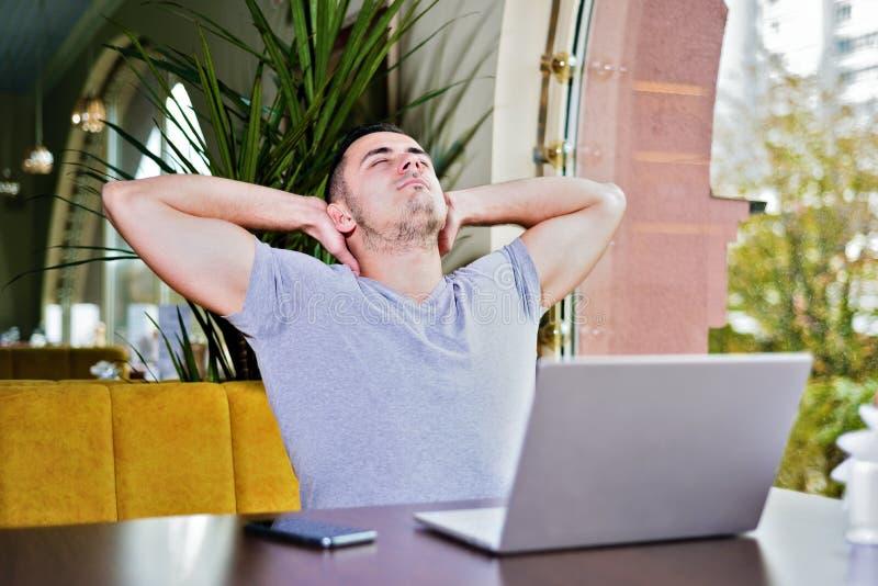 De mens met laptop in koffie ontspant royalty-vrije stock afbeelding