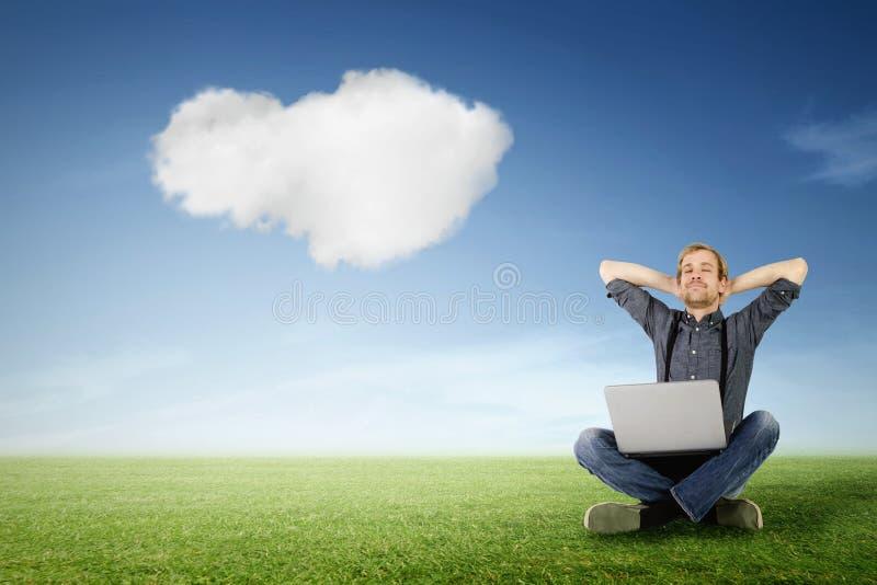 De mens met laptop ontspant op groene weide royalty-vrije stock afbeeldingen