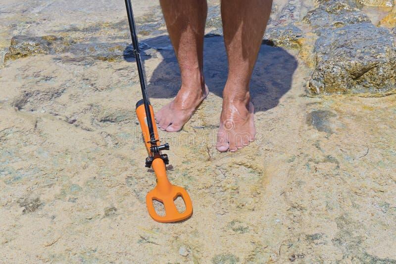 De mens met metaaldetector zoekt verloren schat onder water royalty-vrije stock afbeelding