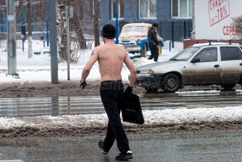 De mens met naakt torso kruist de weg stock foto