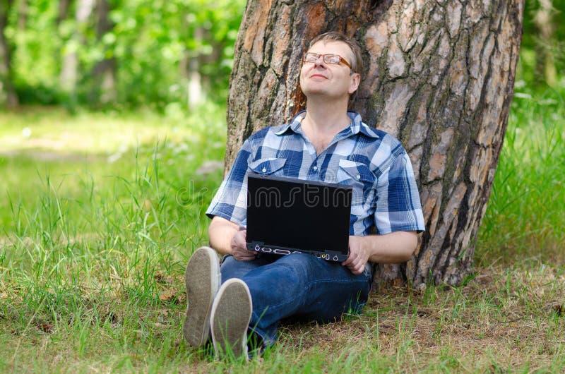 De mens met notitieboekje rust op gazon dichtbij oude pijnboom royalty-vrije stock afbeeldingen