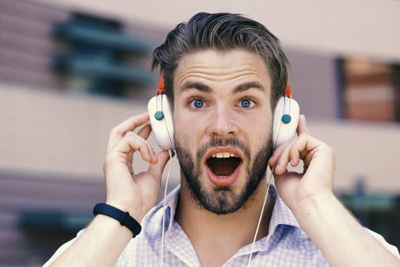 De mens met ongeschoren gezicht geniet van geluid met moderne hoofdtelefoons De macho met verrast gezicht houdt van muziek Jonge  stock fotografie