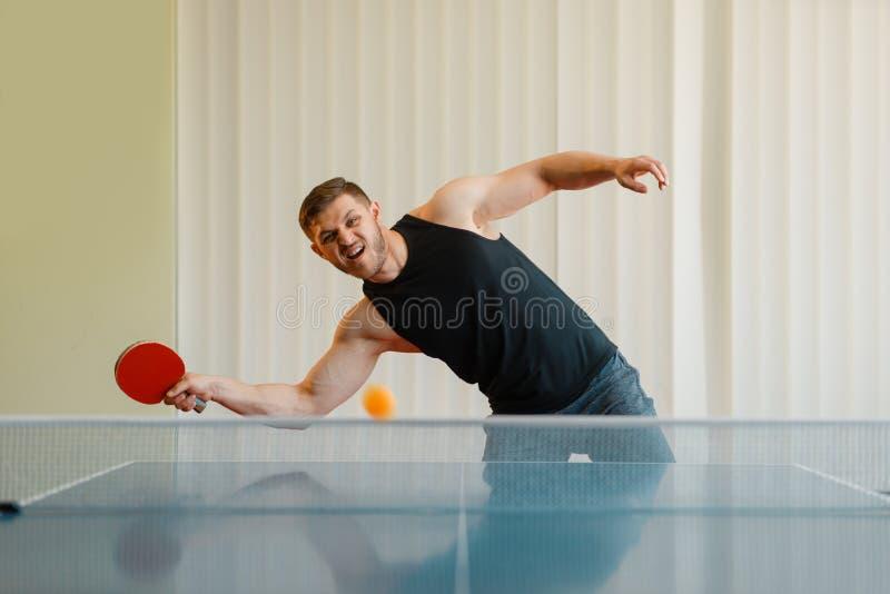 De mens met pingpongracket speelt weg de bal stock fotografie