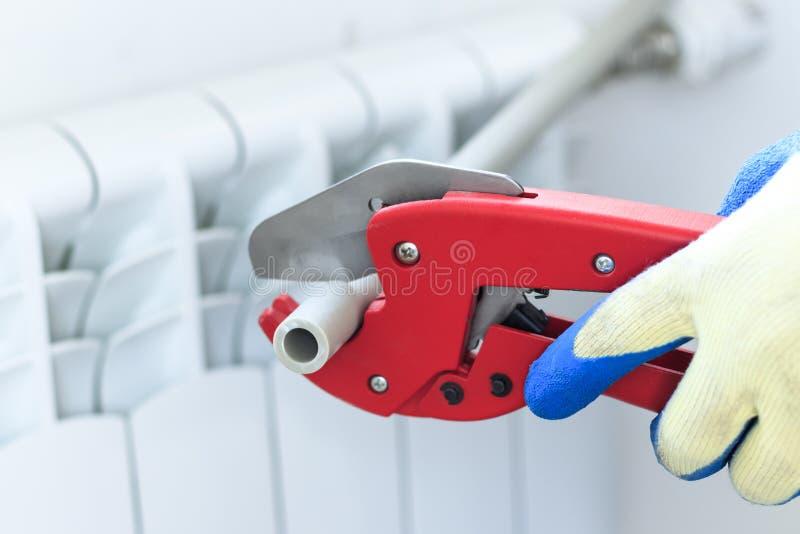 De mens met rode schaar sneed pijpen voor het verwarmen, of water polypropyleen opzettend systeem stock foto's