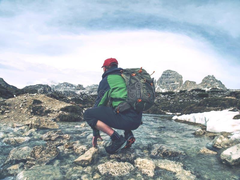 De mens met rugzak beweegt bergrivier stock foto's