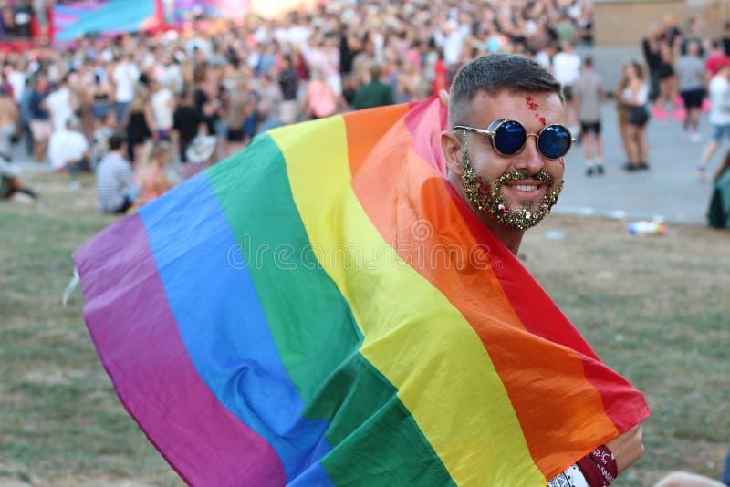 De mens met schittert de regenboogvlag van de baardholding royalty-vrije stock foto