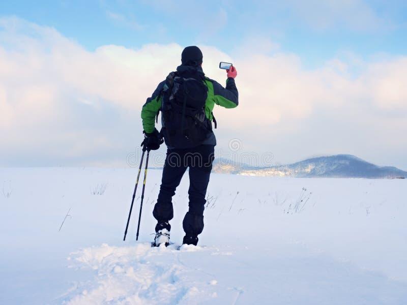 De mens met sneeuwschoenen en de rugzak nemen foto's door smartphone Wandelaar in sneeuwbank royalty-vrije stock foto