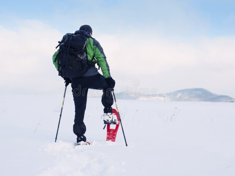 De mens met sneeuwschoenen en de rugzak nemen foto's door smartphone Wandelaar in sneeuwbank royalty-vrije stock afbeeldingen
