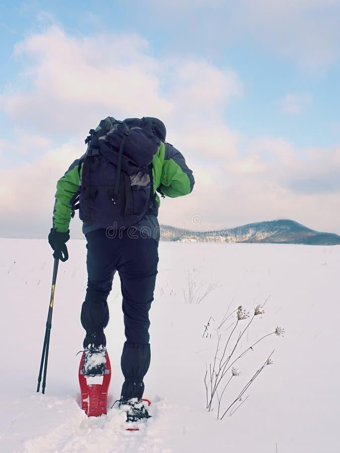 De mens met sneeuwschoenen en de rugzak nemen foto's door smartphone Wandelaar in sneeuwbank royalty-vrije stock foto's
