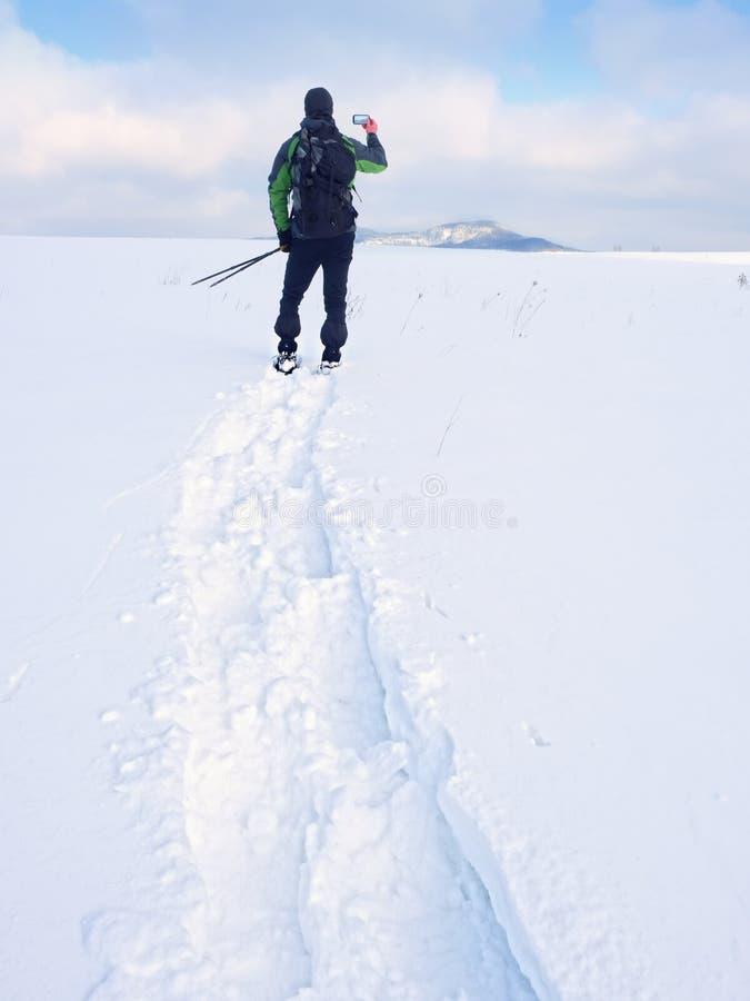 De mens met sneeuwschoenen en de rugzak nemen foto's door smartphone Wandelaar in sneeuwbank stock afbeelding