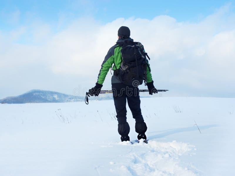 De mens met sneeuwschoenen neemt een rust in sneeuw Wandelaar het snowshoeing stock afbeelding