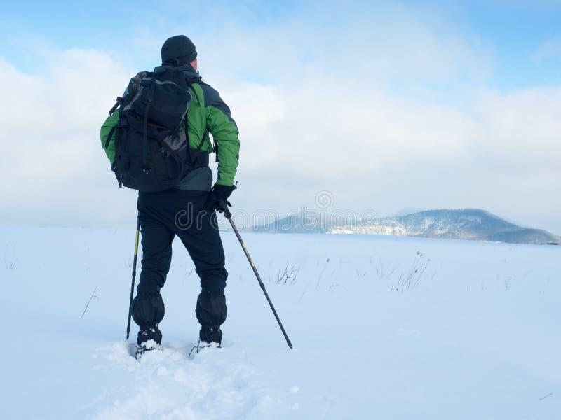 De mens met sneeuwschoenen neemt een rust in sneeuw Wandelaar het snowshoeing stock foto