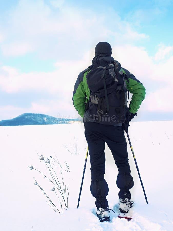 De mens met sneeuwschoenen neemt een rust in sneeuw Wandelaar het snowshoeing royalty-vrije stock fotografie