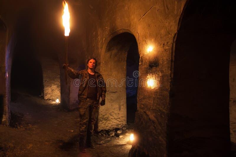 De mens met toorts onderzoekt oude verlaten ondergrondse tempel stock foto