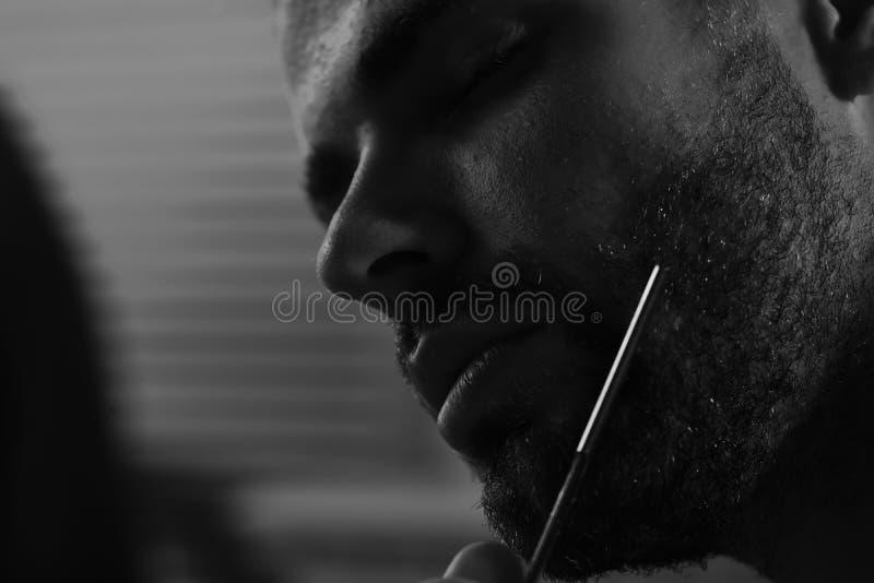 De mens met varkenshaar en dromerig gezicht defocused achtergrond Macho die met dromerig gezicht en gesloten ogen met scheermes s royalty-vrije stock foto