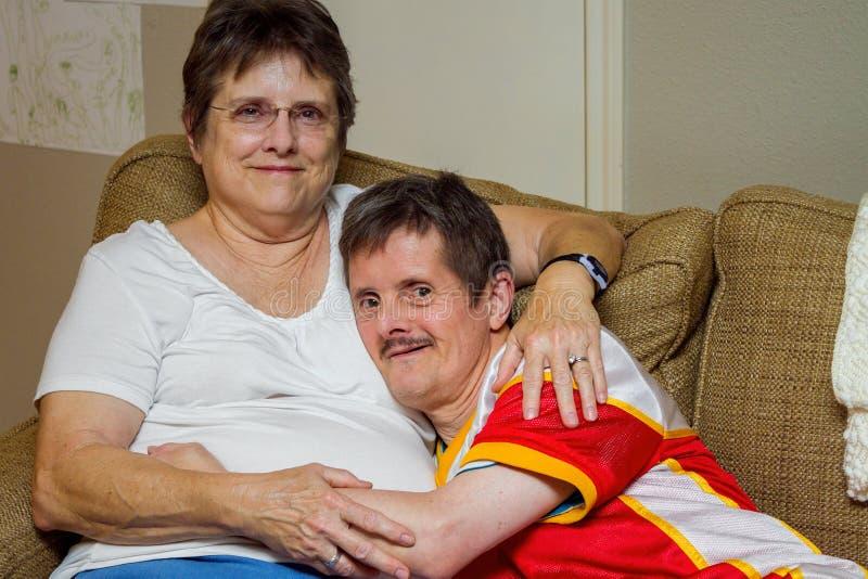 De mens met verslaat Syndroom koestert Zijn Oudere Zuster On een Laag stock foto's