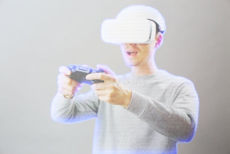 De mens met virtuele werkelijkheidshoofdtelefoon speelt spel Beeld met hologrameffect stock afbeeldingen