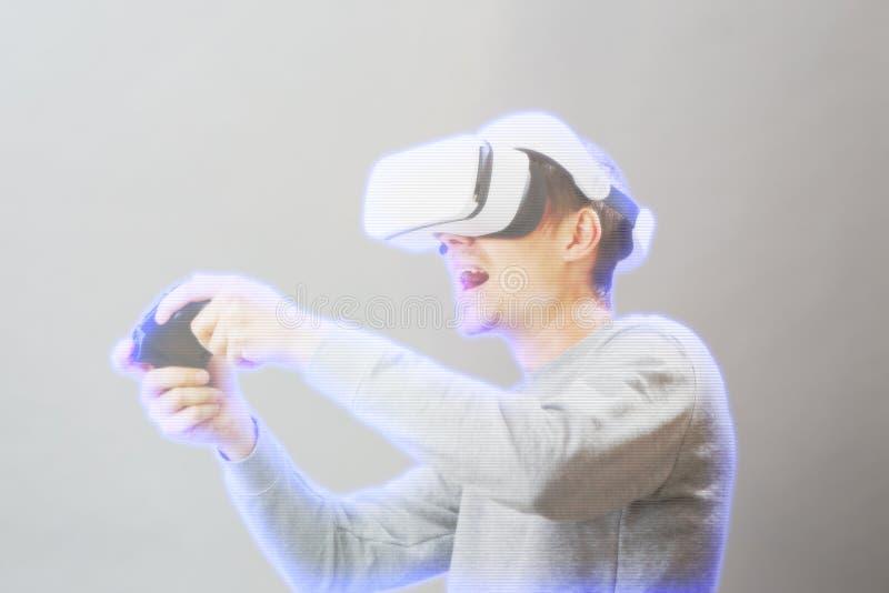 De mens met virtuele werkelijkheidshoofdtelefoon speelt spel Beeld met hologrameffect stock foto