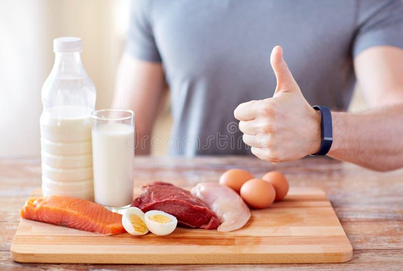 De mens met voedselrijken in het eiwit tonen beduimelt omhoog stock foto's