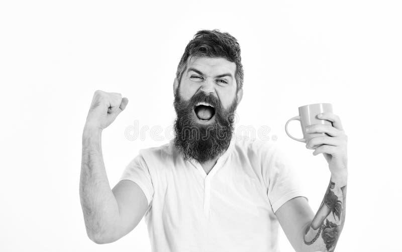 De mens met zich het gelukkige gezicht uitrekken probeert aan wakker met kop van koffie Hipster met baard houdt mok, energiek en  royalty-vrije stock fotografie