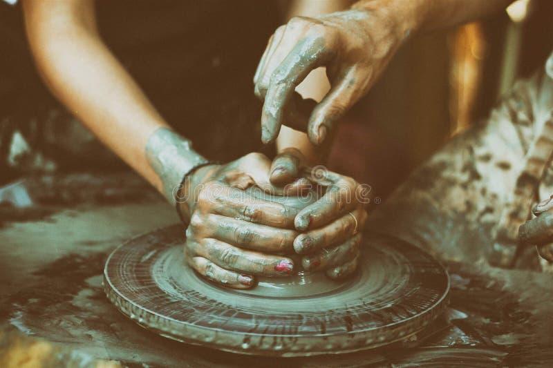 De mens met zijn eigen handen beeldhouwt een stuk van klei op een pottenbakker ` s whe stock foto