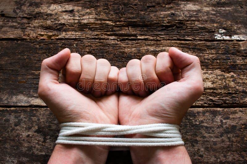 De mens met zijn gebonden hand toont aan dat hij een slaaf is stock afbeeldingen