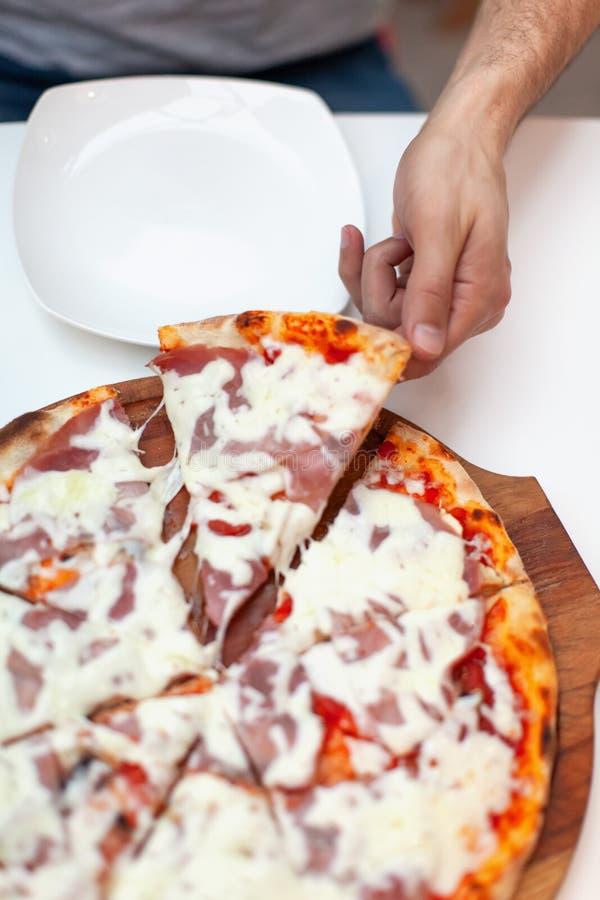 De mens nam eerste plak van heerlijke Italiaanse pizza In kaderhand die plak van hete pizza met ham op houten raad nemen royalty-vrije stock afbeelding