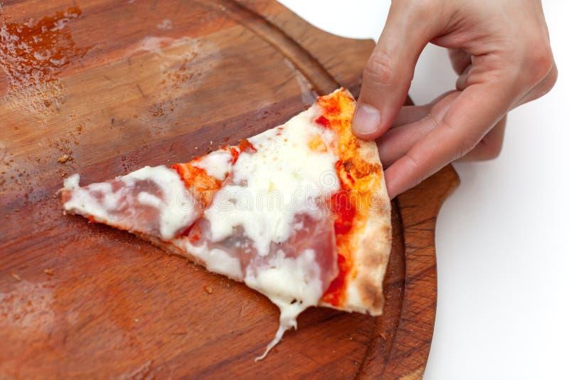 De mens nam laatstgenoemdeplak van heerlijke Italiaanse pizza In kaderhand die plak van hete pizza met ham op houten raad nemen stock afbeelding