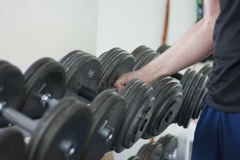 De mens neemt domoorgewicht van rek in gymnastiek op royalty-vrije stock afbeelding
