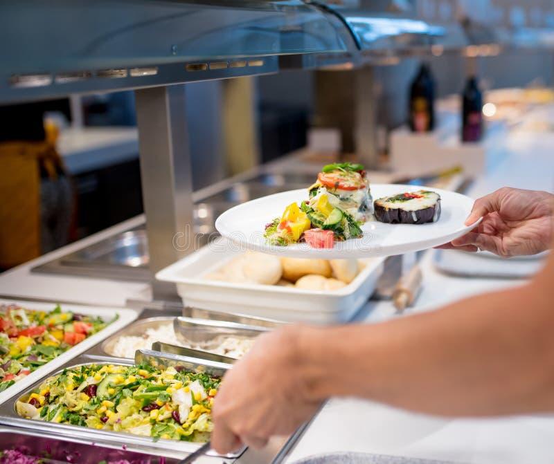 De mens neemt voedsel bij het buffet op royalty-vrije stock foto's
