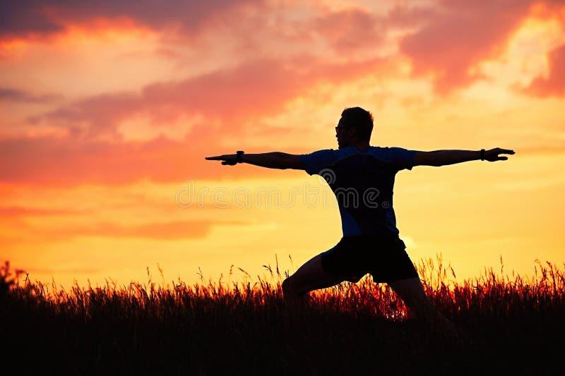 De mens oefent yoga tijdens zonsondergang uit stock foto