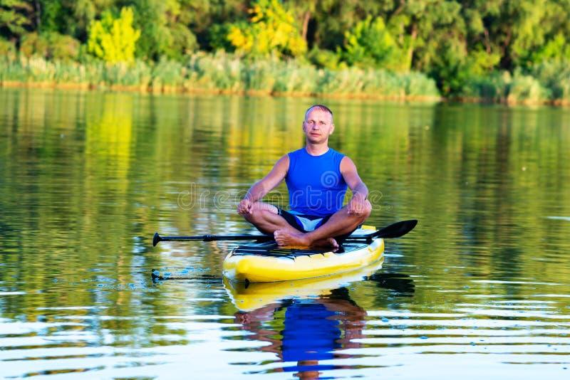 De mens ontspant en mediteert op een SUP raad stock afbeeldingen