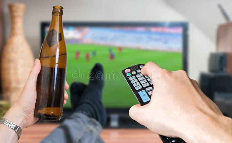 De mens ontspant met benen op lijst en let op voetbalwedstrijd op TV met beer stock fotografie