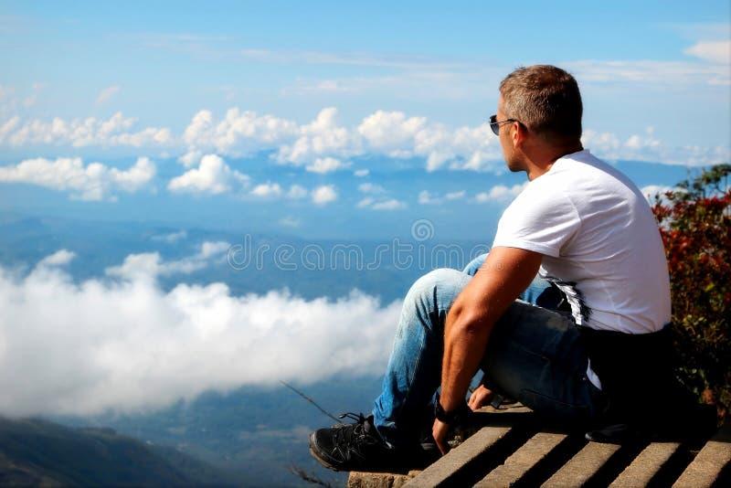 De mens ontspant op de rand van de klip Plateau` Eind van de Wereld `, Sri Lanka stock foto