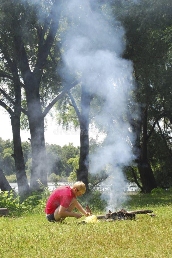 De mens ontsteekt een brand dichtbij de rivier. stock afbeeldingen