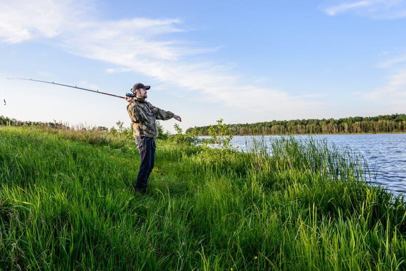 De mens op de rivier werpt een het spinnen visserij royalty-vrije stock foto's