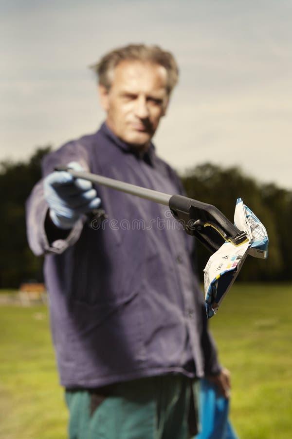 De mens op het werk neemt huisvuil op gras in park op royalty-vrije stock afbeelding