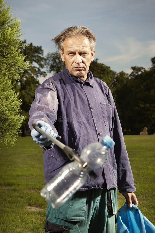 De mens op het werk neemt huisvuil op gras in park op royalty-vrije stock foto's