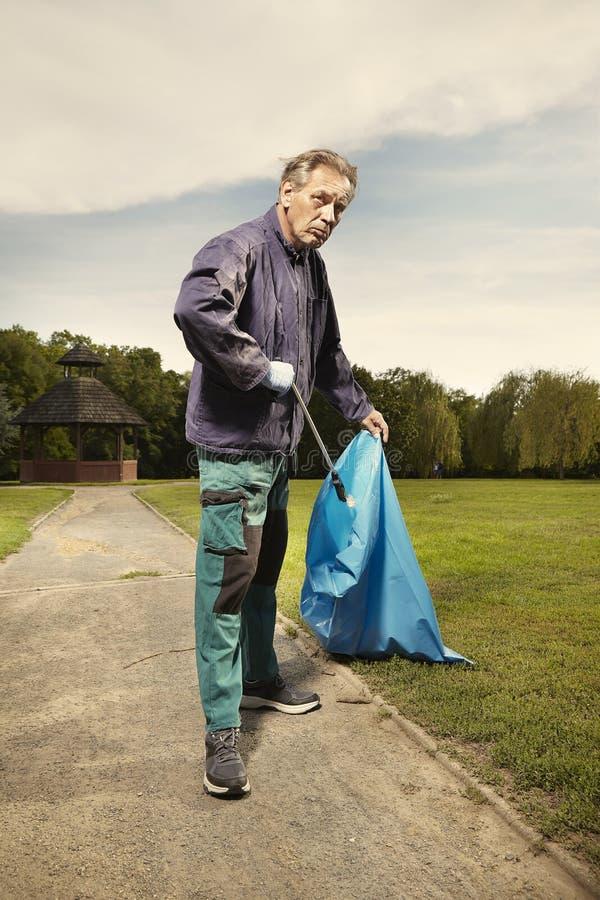 De mens op het werk neemt huisvuil op gras in park op royalty-vrije stock afbeeldingen