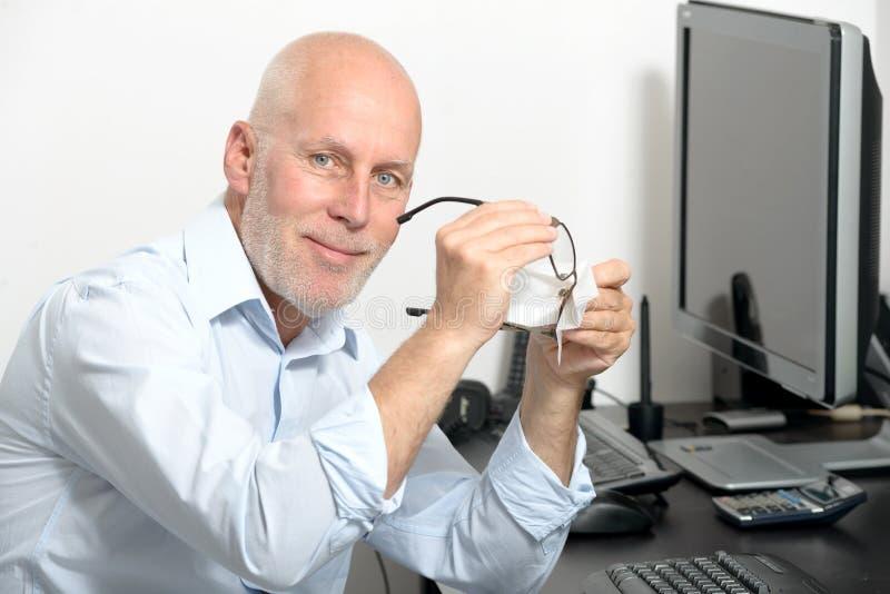 De mens op middelbare leeftijd maakt zijn glazen in zijn bureau schoon royalty-vrije stock afbeelding