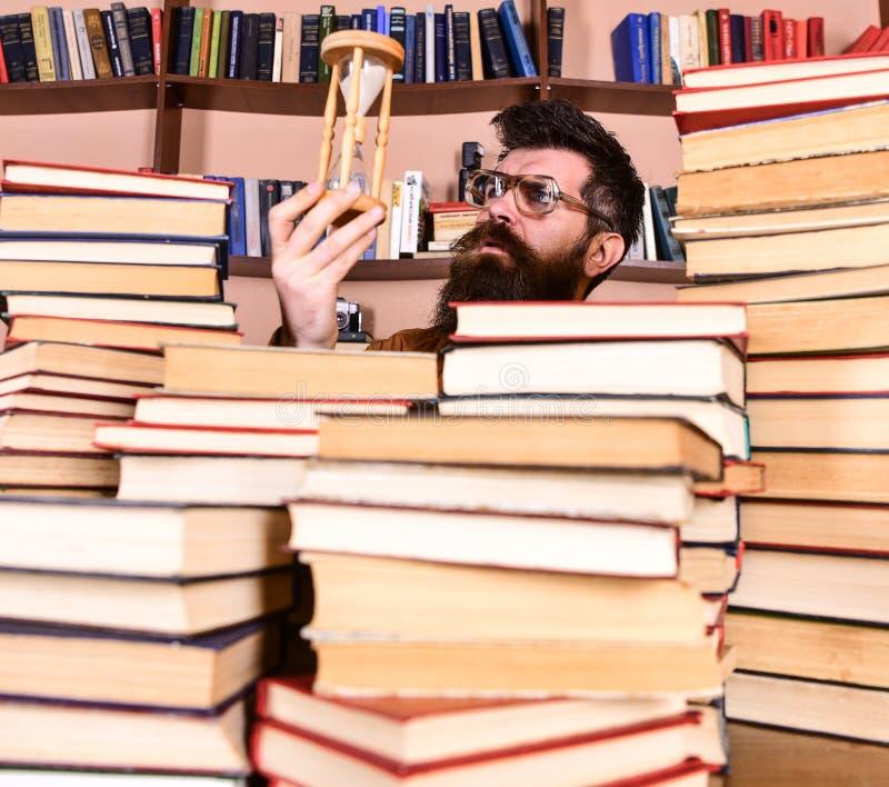De mens op nadenkend gezicht houdt zandloper terwijl het bestuderen, boekenrekken op achtergrond Leraar of student met baard het  stock foto