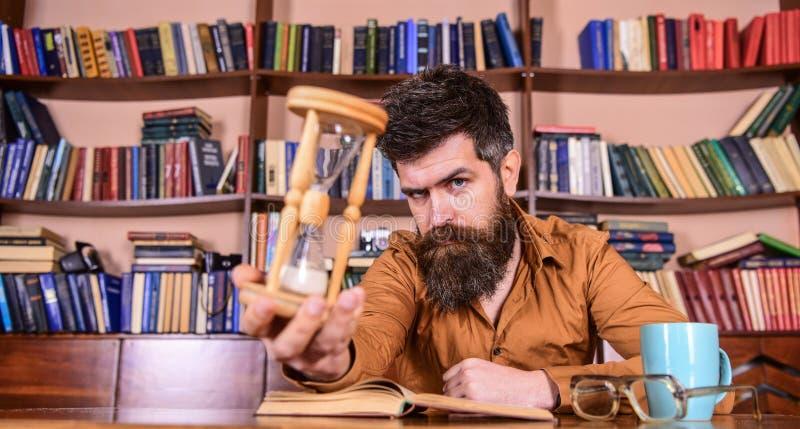 De mens op nadenkend gezicht houdt zandloper terwijl het bestuderen, boekenrekken op achtergrond Leraar of student met baard het  stock afbeeldingen