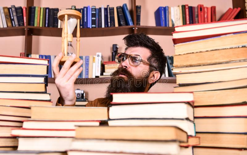 De mens op nadenkend gezicht houdt zandloper terwijl het bestuderen, boekenrekken op achtergrond De mens, wetenschapper in glazen royalty-vrije stock foto's